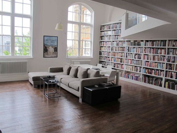 Loft apartment in a converted Victorian school with high ceilings, arched windows and a wall of books.