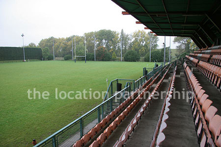 Rugby pitch with very graphic steel stand and huge straight hedge