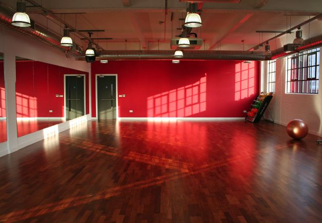 Fitness/ dance studio with warehouse windows letting in lots of natural light. Situated on the third floor.